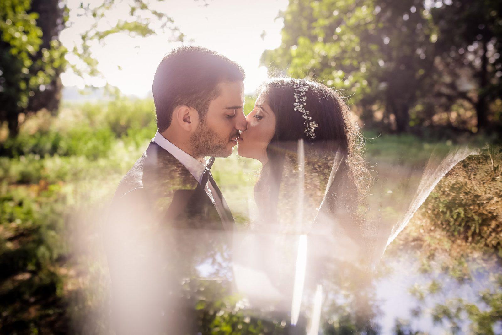 Romantic wedding portrait couple sunset kissing
