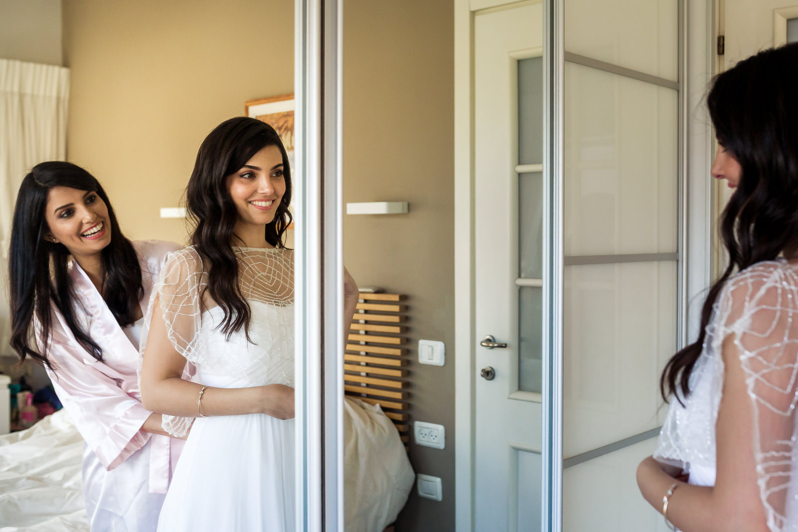 Sister of a bride helps her put wedding dress on her wedding day