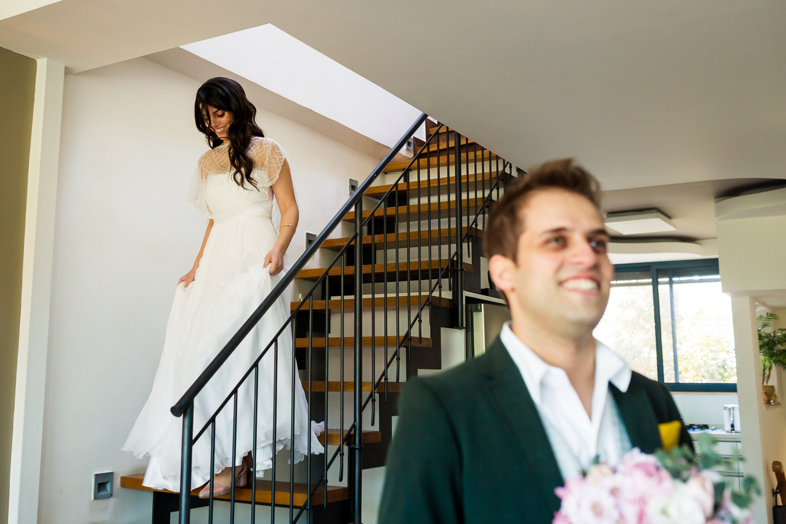 a bride coming down the stairs while her groom smiling with excitement