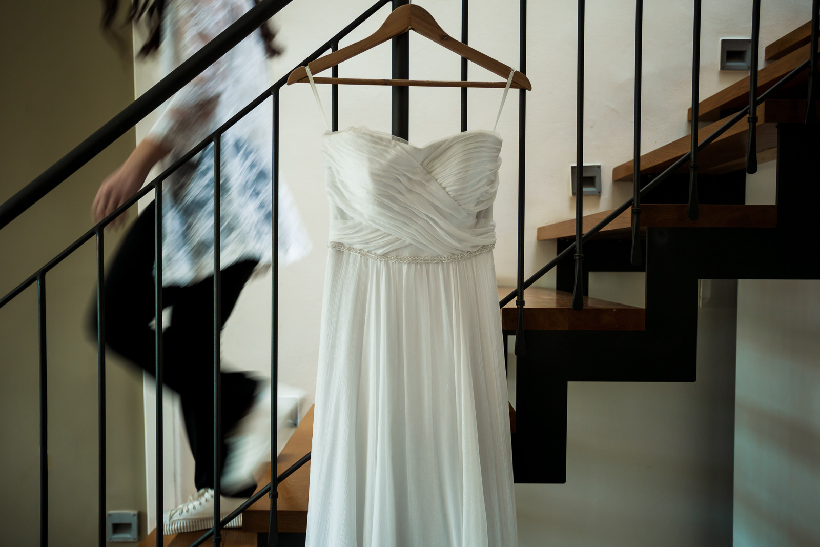 Wedding dress hanging while bride going down the stairs at lower shutter speed
